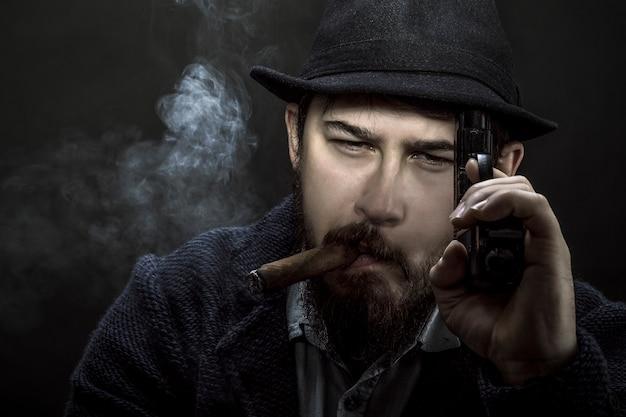 Brodaty gangster w kapeluszu z pistoletem w dłoni i papierosem w ustach na czarnej ścianie