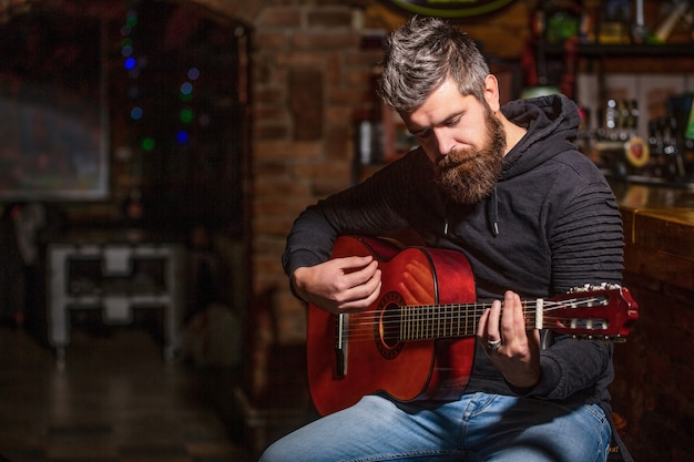 Brodaty gitarzysta gra. grać na gitarze. hipster broda mężczyzna siedzi w pubie. muzyka na żywo. gitary i struny. brodaty mężczyzna gra na gitarze, trzymając w rękach gitarę akustyczną. koncepcja muzyki.