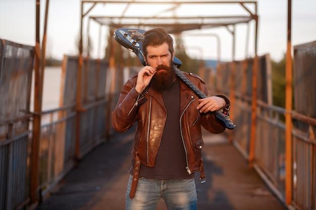Brodaty gitarzysta o siwych włosach w brązowej skórzanej kurtce i niebieskich dżinsach trzyma czarną gitarę elektryczną na ramieniu i prostuje wąsy