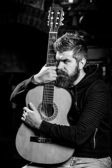 Brodaty gitarzysta trzymający gitarę akustyczną.