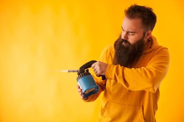 Brodaty handy man trzyma latarkę ciosową na żółtym tle. profesjonalne narzędzie. niebieskie narzędzie