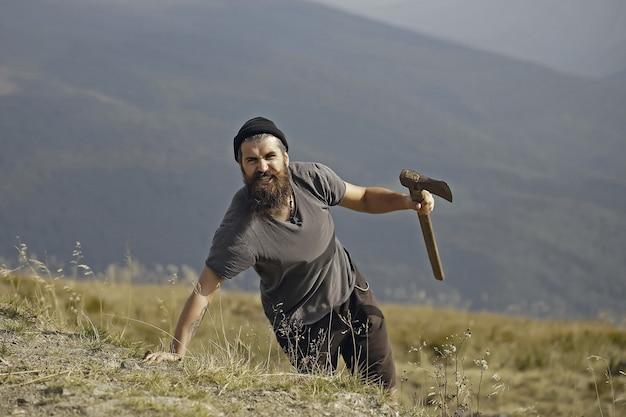 Brodaty hipster mężczyzna w kraciastej koszuli z długą brodą, trzymając topór na szczycie góry na naturalny