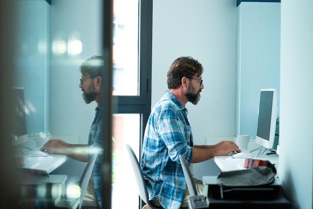 Brodaty hipster styl dorosły mężczyzna pracujący pisanie na komputerze stacjonarnym w biurze w obszarze roboczym sam - ludzie i nowoczesna praca połączenie internetowe styl życia - niezależny dom siedzący mężczyzna pisania na klawiaturze