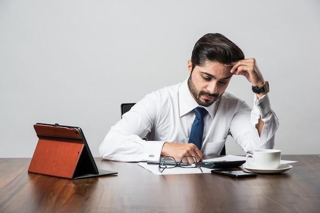 Brodaty indyjski biznesmen księgowy siedząc przy biurku w biurze