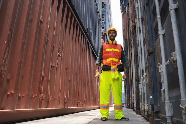 Brodaty inżynier stojący w żółtym hełmie do kontroli załadunku i sprawdzania jakości pojemników