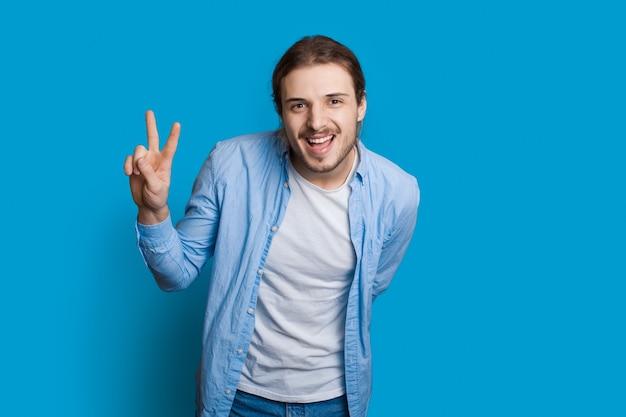 Brodaty kaukaski mężczyzna gestykuluje znak powitania i pokoju, uśmiechając się do kamery na niebieskiej ścianie w zwykłych ubraniach