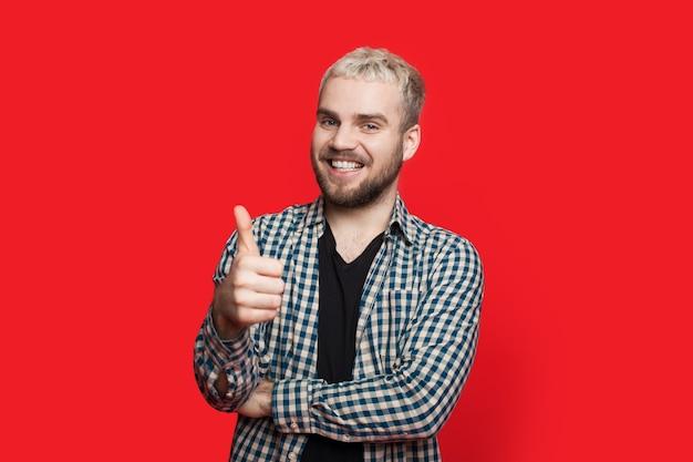 Brodaty kaukaski mężczyzna o blond włosach pokazuje podobny znak na czerwonej ścianie