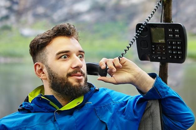 Brodaty kaukaski mężczyzna rozmawia przez stary model telefonu z przyciskiem, z rurką na skręconym drucie.