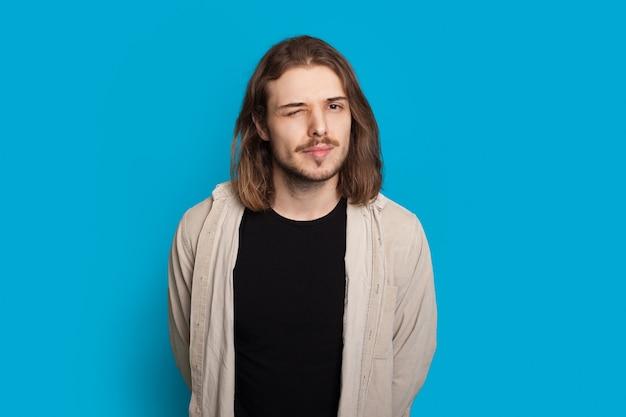 Brodaty kaukaski mężczyzna z długimi włosami miga, pozując na niebieskim tle