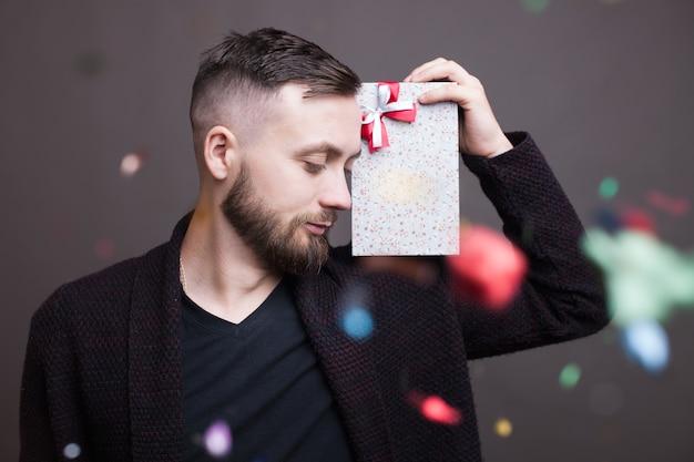 Brodaty kaukaski mężczyzna z prezentem na ramieniu pozuje w formalnym stroju na szarej ścianie studia z konfetti