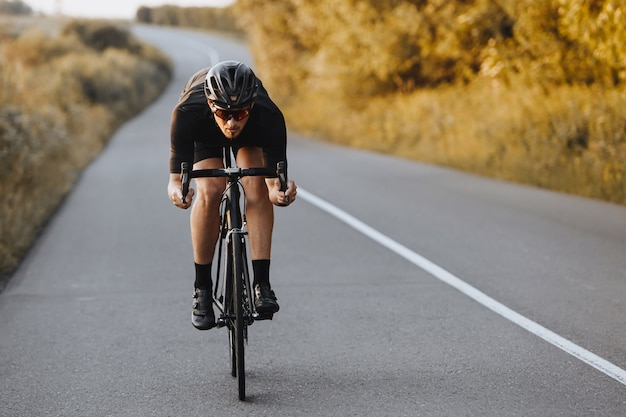 Brodaty kolarz zawodowy w stroju sportowym i kasku ochronnym aktywnie jeżdżący po utwardzonej drodze.