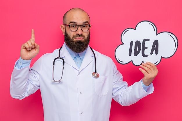 Brodaty lekarz mężczyzna w białym fartuchu ze stetoskopem na szyi w okularach trzymający znak dymku z pomysłem na słowo zaskoczony, pokazując palec wskazujący z nowym pomysłem