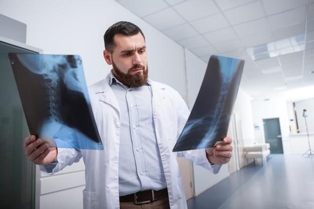 Brodaty lekarz spacerujący w korytarzu szpitala, badając skany rentgenowskie