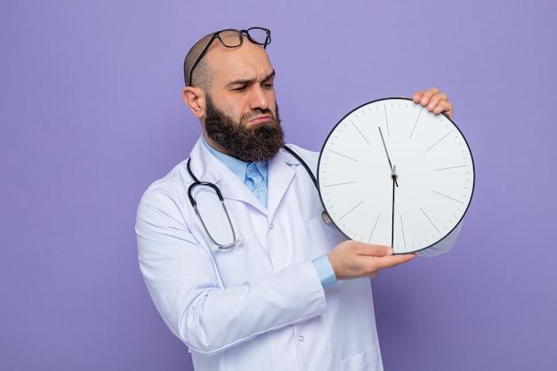 Brodaty lekarz w białym fartuchu ze stetoskopem na szyi trzymający zegar patrząc na niego niezadowolony i zdezorientowany stojąc na fioletowym tle