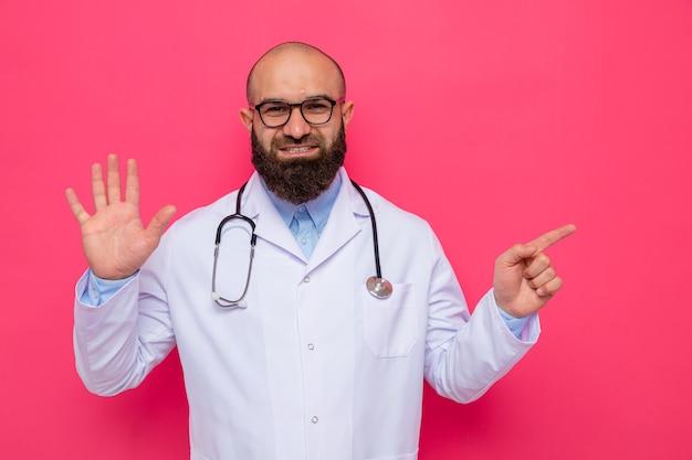 Brodaty lekarz w białym fartuchu ze stetoskopem na szyi w okularach pokazujący piąty z dłonią wskazującą palcem wskazującym w bok, uśmiechnięty pewnie