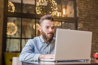 Brodaty młody człowiek pracuje na laptopie