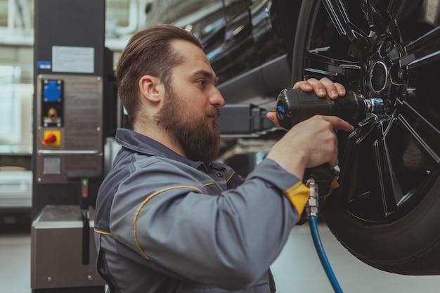 Brodaty mechanik pracuje na stacji obsługi samochodów