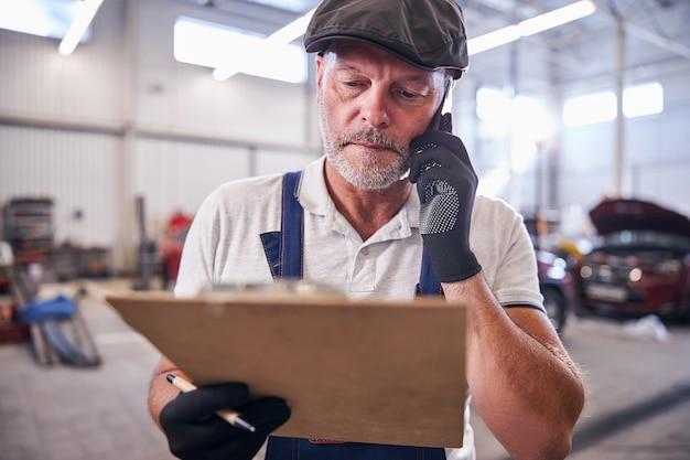 Brodaty mechanik prowadzący rozmowę telefoniczną w warsztacie samochodowym