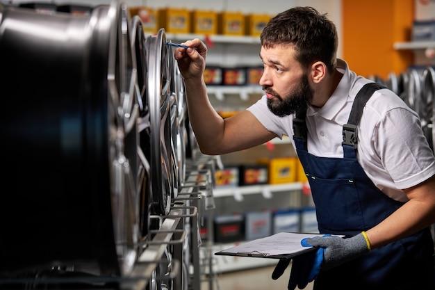 Brodaty mechanik samochodowy w mundurze pewnie sprawdza dyski samochodowe reprezentowane na sprzedaż w serwisie, bada i pilnuje towarów