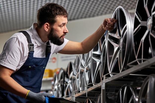 Brodaty mechanik samochodowy w mundurze sprawdza dyski samochodowe reprezentowane na sprzedaż w serwisie, bada, pilnuje towarów