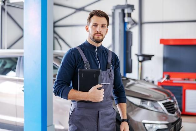 Brodaty mechanik w kombinezonie stojący w garażu salonu samochodowego i trzymający tablet