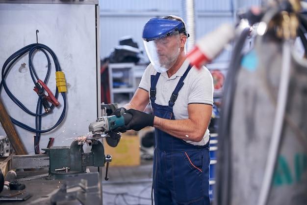 Brodaty mechanik w masce ochronnej używający szlifierki w garażu