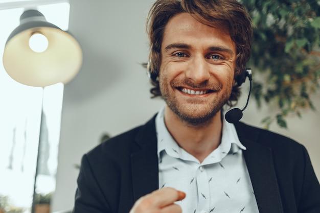 Brodaty mężczyzna biznesmen z zestawem słuchawkowym o rozmowie biznesowej online z bliska