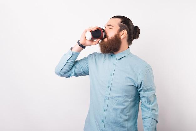 Brodaty mężczyzna biznesu cieszy się jego kawa na wynos.