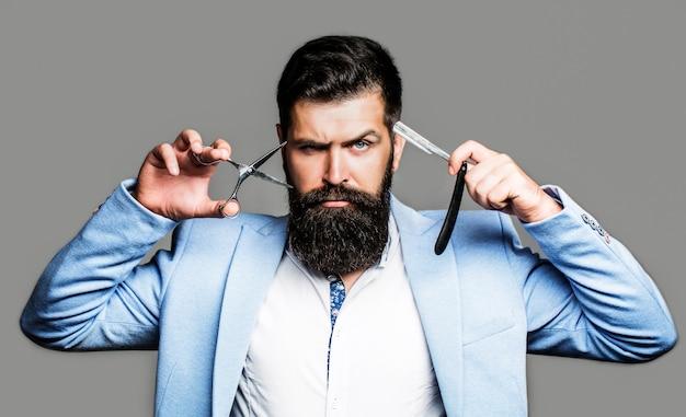 Brodaty mężczyzna, brodaty mężczyzna. portret mężczyzny broda. nożyczki fryzjerskie i brzytwa, fryzjer, garnitur.