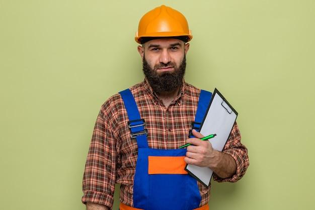 Brodaty mężczyzna budowniczy w mundurze budowlanym i kasku ochronnym, trzymający schowek z piórem, uśmiechnięty pewnie