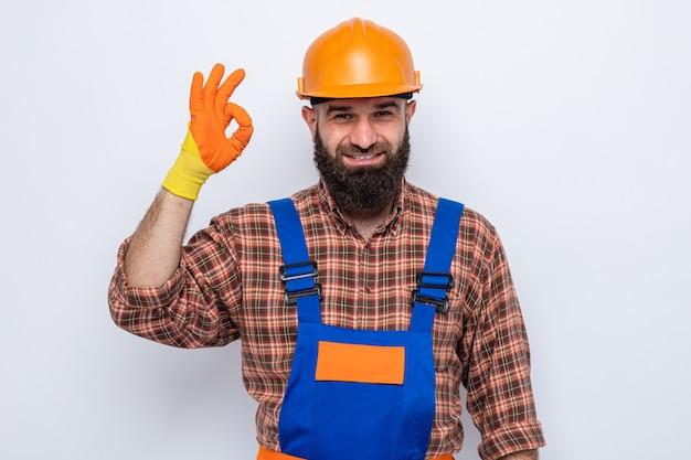 Brodaty mężczyzna budowniczy w mundurze budowlanym i kasku ochronnym w gumowych rękawiczkach, patrząc na kamerę szczęśliwy i pozytywny, pokazując znak ok uśmiechający się, stojąc na białym tle