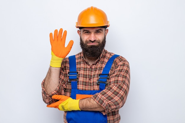 Brodaty mężczyzna budowniczy w mundurze budowlanym i kasku ochronnym w gumowych rękawiczkach, patrząc na kamerę, uśmiechając się radośnie machając ręką stojącą na białym tle