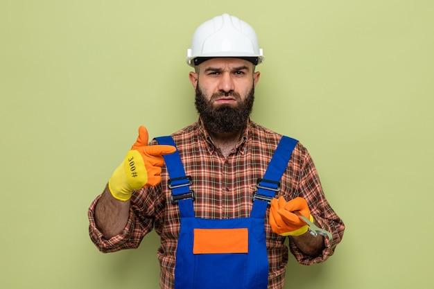 Brodaty mężczyzna budowniczy w mundurze budowlanym i kasku ochronnym w gumowych rękawiczkach, trzymając klucz wskazujący palcem wskazującym na to, patrząc na kamerę z poważną twarzą stojącą na zielonym tle