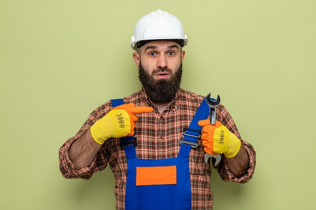 Brodaty mężczyzna budowniczy w mundurze budowlanym i kasku ochronnym w gumowych rękawiczkach, trzymając klucz wskazujący palcem wskazującym na to patrząc zaskoczony, stojąc na zielonym tle