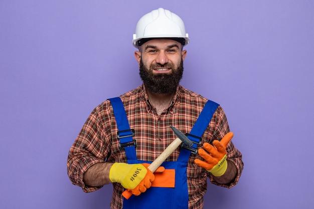 Brodaty mężczyzna budowniczy w mundurze budowlanym i kasku ochronnym w gumowych rękawiczkach, trzymając młotek, patrząc na kamerę, uśmiechając się radośnie szczęśliwy i pozytywnie stojąc na fioletowym tle