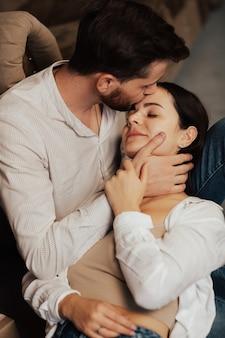 Brodaty mężczyzna całuje swoją kobietę w czoło, a ona uśmiecha się z zamkniętymi oczami.