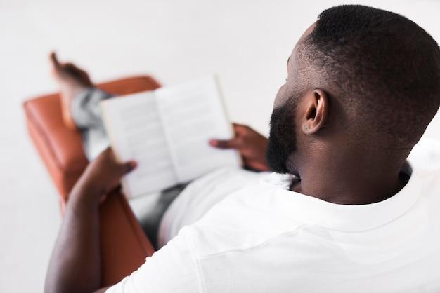 Brodaty mężczyzna cieszy się czytający w domu