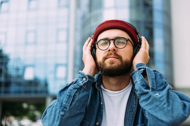 Brodaty mężczyzna cieszy się muzyką z zamkniętymi oczami w słuchawkach na zewnątrz w mieście. pokój na tekst.
