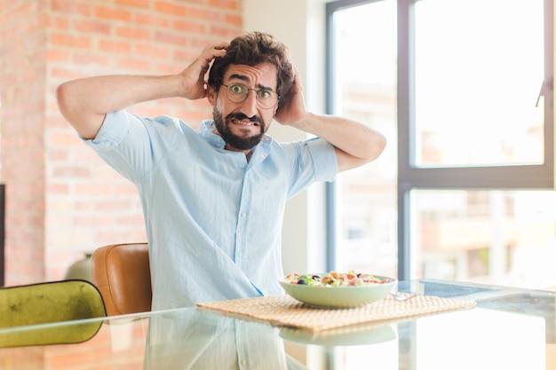 Brodaty mężczyzna czuje się zestresowany, zmartwiony, zaniepokojony lub przestraszony, z rękami na głowie, panikuje podczas pomyłki