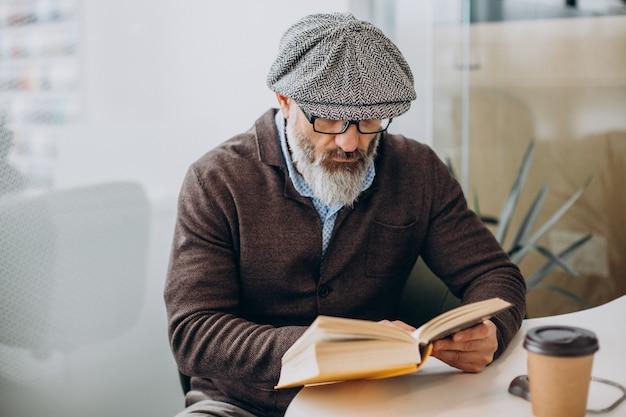 Brodaty mężczyzna czyta książkę i siedzi przy stole