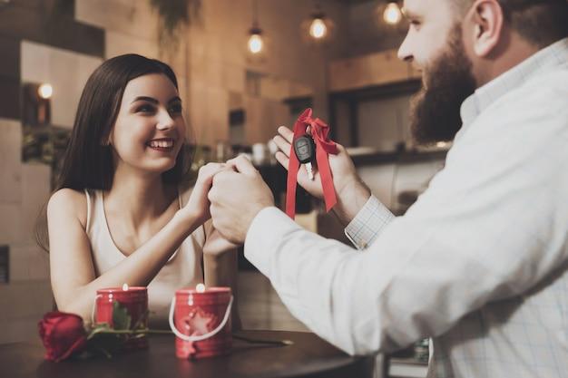 Brodaty mężczyzna daje prezent dla pięknej dziewczyny