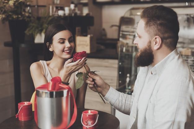 Brodaty mężczyzna daje róży pięknej uśmiechniętej dziewczyny