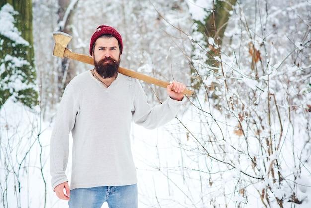 Brodaty mężczyzna. drwal w zimowym lesie. brodaty hipster z siekierą. poważny drwal na zimowy dzień na świeżym powietrzu.
