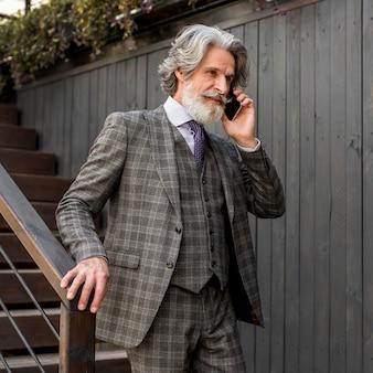 Brodaty mężczyzna elegancki rozmawia przez telefon