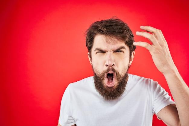Brodaty mężczyzna gestykuluje rękami białą koszulkę wyraz twarzy agresji czerwony na białym tle