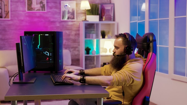 Brodaty mężczyzna grający w gry wideo w pokoju z kolorowymi neonami. mężczyzna rozmawia z przyjaciółmi podczas grania w gry wideo.