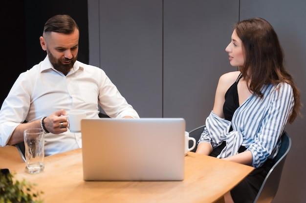 Brodaty mężczyzna i piękna kobieta siedzą w nowoczesnym biurze z laptopem i patrzą na siebie podczas rozmowy