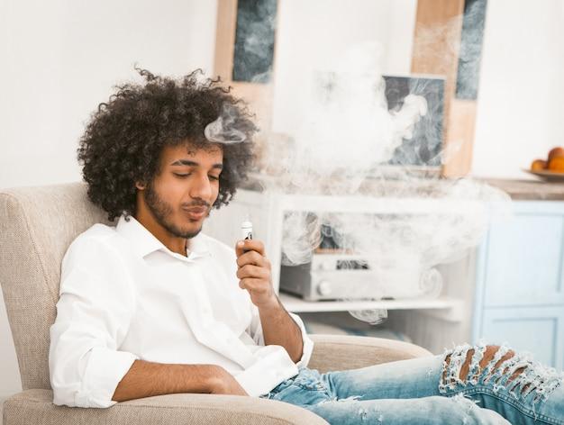Brodaty mężczyzna korzystających z zaciągów dymu elektronicznego papierosa.