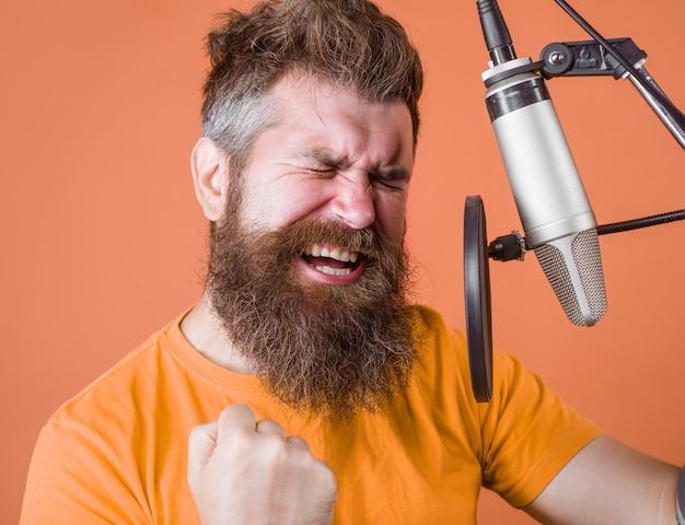 Brodaty mężczyzna krzyczy do mikrofonu mężczyzna karaoke śpiewa z mikrofonem śpiewa w mikrofonie studyjnym