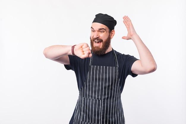 Brodaty mężczyzna kucharz patrząc boi się na smartwatch na białym